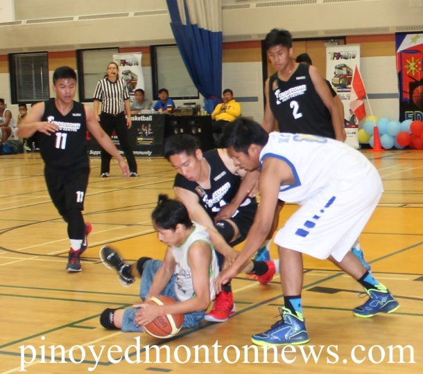 Grande Prairie's JP Cruz protects the ball from Crosstown's JR Eje in this bit of action of the 2nd Edson Filipino Inter-Town Basketball League, Sunday.(Photo by Moses Billacura/pinoy edmonton news)
