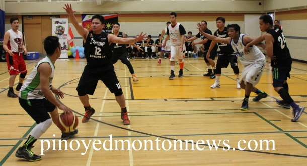 Grande Prairie's Dominic Macarine looks for an open man as he is closely guarded by Crosstown Auto's Sarce Garcia(No.12) in the final game of the 2nd Edson Filipino Inter-Town Basketball League, Sunday.(Photo by Moses Billacura/pinoy edmonton news)