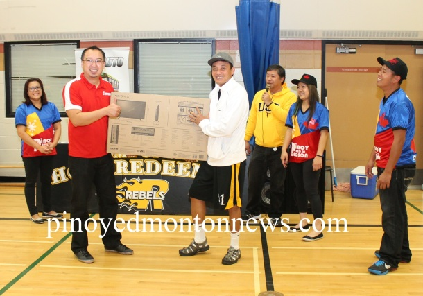 Antonio Nuyda of Grande Prairie team happily receives the raffle prize from Crosstown Auto's Chester Tiongson. In the photo are organizers Aileen Gabito, Joey Manalang, Rande Cagalitan and Rodel Gravides.(Photo by Moses Billacura/pinoy edmonton news)